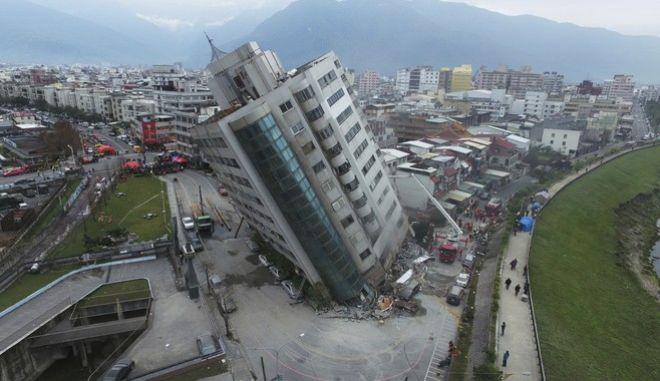 A residential building leans on a collapsed first floor following an earthquake, Wednesday, Feb. 7, 2018, in Hualien, southern Taiwan. Rescue crews continue to try free people from damaged buildings after a strong earthquake hit near Taiwan's east coast and killed at least four people. (Central News Agency via AP)
