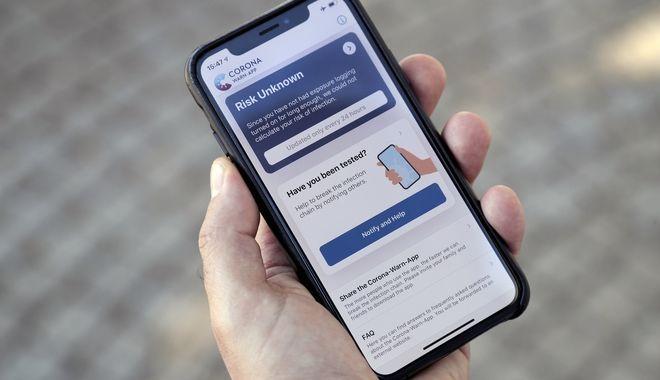 Άντρας κρατά ένα smartphone, όπου έχει κατεβάσει την επίσημη εφαρμογή της γερμανικής κυβέρνησης «Corona Warn-App» (Corona Warning Application) στο Βερολίνο της Γερμανίας, 15 Ιουνίου 2020.