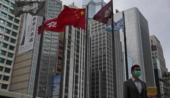 Άντρας φορά προστατευτική μάσκα προσώπου κάτω από την κινεζική σημαία