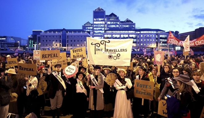 People carry various signs as they take part in a march calling for the repeal of the 8th amendment to the Irish constitution, in Dublin, Thursday, March 8, 2018. Ireland's 8th Amendment enshrines the right to life of the unborn - a provision that renders abortion illegal other than in exceptional circumstances. (Niall Carson/PA via AP)