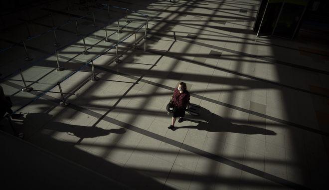 Γυναίκα περπατάει σε άδειο αεροδρόμιο