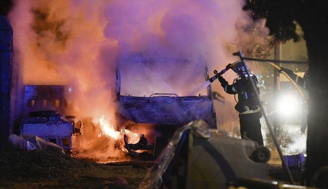 Πυροσβέστες επιχειρούν για την κατάσβεση φωτιάς σε οχήματα που πυρπολήθηκαν κατά τις εντάσεις στην Νάντη