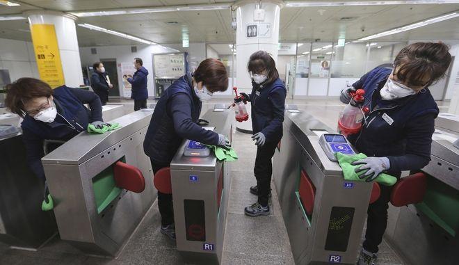 Οι εργαζόμενοι απολυμαίνουν τις πύλες των εισιτηρίων με την ελπίδα να αποτρέψουν τη εξάπλωση του κοροναϊού σε σταθμό μετρό στη Σεούλ της Νότιας Κορέας
