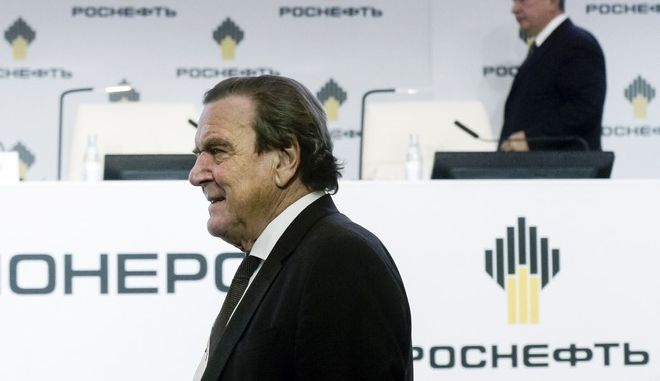 Former German Chancellor Gerhard Schroeder, newly elected chairman of the board of directors of Russia's oil giant Rosneft, foreground, and Rosneft CEO Igor Sechin, right, arrive to attend an extraordinary shareholders meeting in St. Petersburg, Russia, Friday, Sept. 29, 2017. Schroeder has been named the new chairman of Russian state oil giant Rosneft, Russian news agencies reported Friday. (Olga Maltseva/Pool Photo via AP)