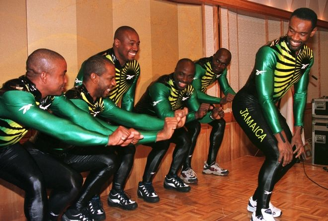 Dudley Stokes, captain of the Jamaican bobsled team for the Nagano Winter Olympics, right, smiles back at his team members as they demonstrate the bobsled pushing form during a sending-off reception for the team at a Tokyo hotel Wednesday, Feb. 4, 1998.   The Jamaican team which has trained in Germany competes in the Winter Games starting Feb. 7 in central Japan.   (AP Photo/Koji Sasahara)