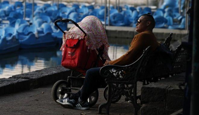 Ένας άντρας κάθεται σε ένα παγκάκι προσέχοντας το παιδί του στο Μεξικό