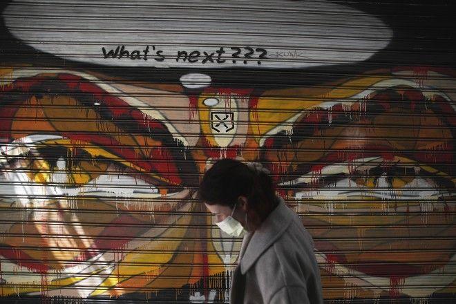 Γυναίκα με μάσκα μπροστά σε γκράφιτι στην Αθήνα.