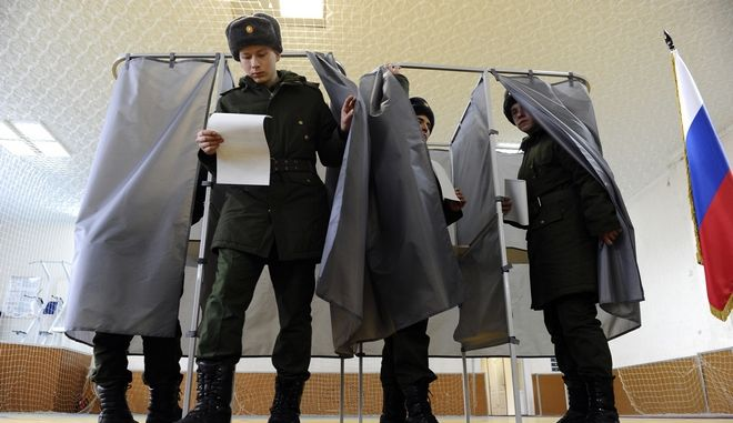 Russian soldiers exit a polling booth as they prepare to cast their ballots in the presidential election in Rostov-ojn-Don, Russia, Sunday, March 18, 2018. Russia's presidential election was tainted Sunday by unprecedented pressure on voters to turn out and incidents of suspected ballot box stuffing, a barely democratic exercise that will grant Vladimir Putin another six years of power. (AP Photo)