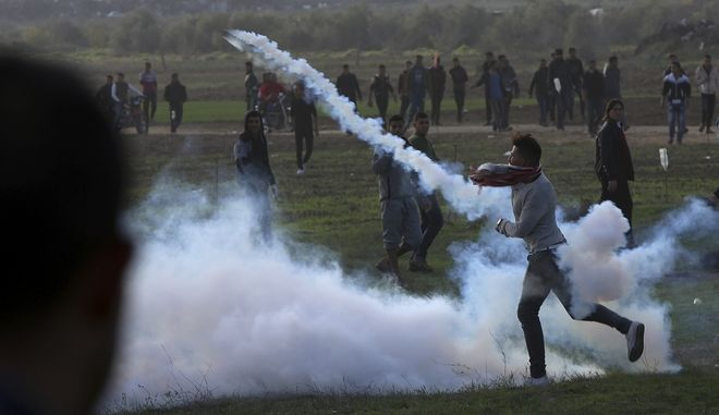 A Palestinian protester throws back a teargas canister that was fired by Israeli soldiers, during clashes on the Israeli border following a protest against U.S. President Donald Trump's decision to recognize Jerusalem as the capital of Israel, east of Gaza City, Friday, Dec. 15, 2017. (AP Photo/Adel Hana)