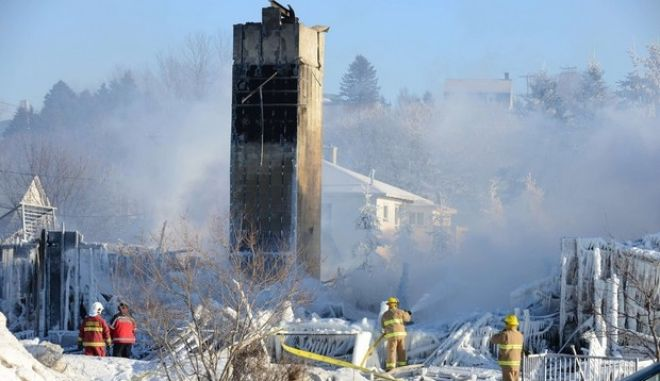 TOPSHOTS Canadian firefighters douse the burnt remains of a retirement home in L'Isle-Verte on January 23, 2014. Firefighters searched the ashes of a Quebec retirement home that burned to the ground on a bleak midwinter night, leaving more than 30 residents feared dead. Officials said the remains of three victims had been recovered and some 30 more were unaccounted for, while the local fire chief said rescuers were now searching for bodies.     AFP PHOTO/Remi SENECHALRemi Senechal/AFP/Getty Images ORG XMIT: