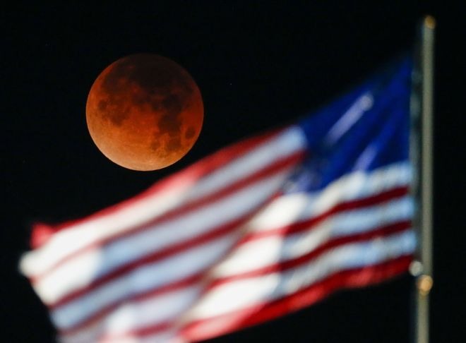 A rare occurrence called a 'Super Blue Blood Moon' is seen behind the U.S. flag at Santa Monica Beach in Santa Monica, Calif., Wednesday, Jan. 31, 2018. It's the first time in 35 years a blue moon has synced up with a supermoon and a total lunar eclipse. Hawaii and Alaska have the best seats, along with the Canadian Yukon, Australia and Asia. The western U.S. should have good viewing, too, along with Russia. The U.S. East Coast, Europe and most of South America and Africa are out of luck for the eclipse. (AP Photo/Ringo H.W. Chiu)