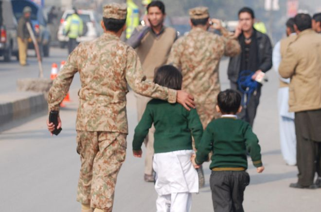 A soldier escorts schoolchildren after they were rescued from the Army Public School that is under attack by Taliban gunmen in Peshawar, December 16, 2014. Taliban gunmen in Pakistan took hundreds of students and teachers hostage on Tuesday in a school in the northwestern city of Peshawar, military officials said.  REUTERS/Khuram Parvez (PAKISTANCIVIL LAW - Tags: EDUCATION CIVIL UNREST CRIME LAW)