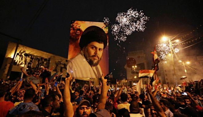 Υποστηρικτές του σιήτη κληρικού αλ Σαντρ σε συγκέντρωση στην πλατεία Ταχρίρ της Βαγδάτης μετά την ανακοίνωση των αποτελεσμάτων που φέρνουν το συνδυασμό του πρώτο στις βουλευτικές εκλογές