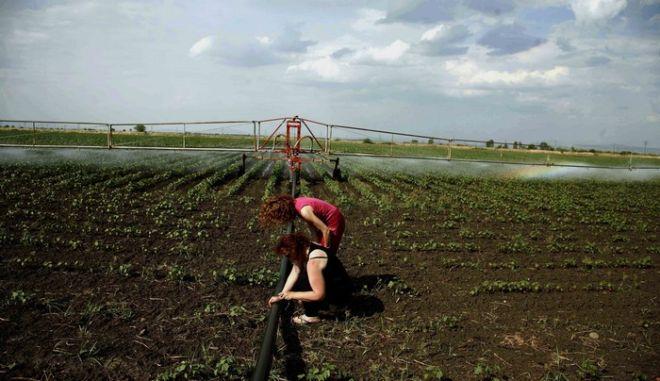 Αγρότισσες τσεκάρουν τα μηχανήματα ποτίσματος στα χωράφια της πεδιάδας στην περιοχή της Καρδίτσας