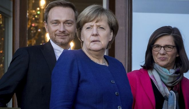 Chancellor Angela Merkel, center, Free Demoratic Party chairman Christian Lindner, left, and Katrin Goering-Eckardt, group chairwoman of the Greens in the parliament stand  on the balcony of the German parliamentary society prior to exploratory talks  in Berlin, Monday, Oct. 30, 2017.  Germany's Sept. 24 election left Chancellor Angela Merkel trying to form an untried coalition that brings together her conservative Union bloc, the pro-business Free Democrats and the traditionally left-leaning Greens. ( Michael Kappeler/dpa via AP)