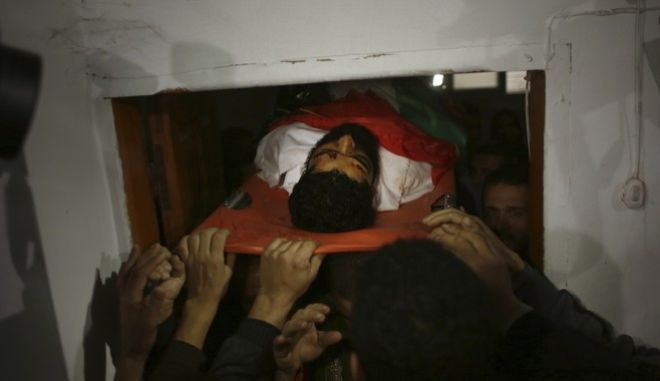 Palestinian mourners carry the body of 29-year-old activist Ibrahim Abu Thuraya who was shot and killed by Israeli troops Friday, in clashes on the Israeli border with Gaza, during his funeral in Gaza City, Saturday, Dec. 16, 2017. Abu Thuraya lost legs and an eye in Israeli bombing during the 2008 Israel and Gaza war. (AP Photo/ Khalil Hamra)
