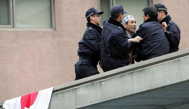 """A South Korean protester Oh Sung-taek, center, is arrested by police after he climbed over the walls of the Japanese Embassy compound in Seoul, South Korea, Wednesday, March 21, 2007. Japanese Prime Minister Shinzo Abe triggered outrage across Asia earlier this month by saying there was no proof the women, including some Australians, were coerced into prostitution. He later said Japan will not apologize again for the military's """"comfort stations."""" (AP Photo/Ahn Young-joon)"""
