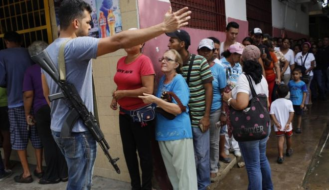 In this Nov. 4, 2016 photo, a security officer from the anti-extortion and kidnapping command of the National Guard (CONAS), gives instructions to residents lining up to buy food at a store in downtown Cumana, Sucre state, Venezuela. CONAS agents provide security for arriving food trucks after the state became the epicenter of food riots that swept through the country over the summer. (AP Photo/Rodrigo Abd)