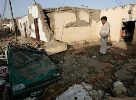 c4839f3bd4 A man watches a car destroyed by an earthquake in Pisco