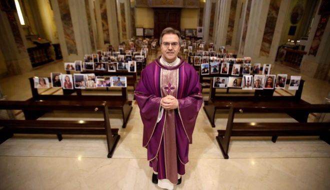 Ο ιερέας Τζουζέπε Κομπάρι κάνει λειτουργίες έχοντας φωτογραφίες ενοριτών του στις καρέκλες της άδειας εκκλησίας