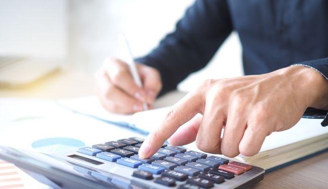 Φορολογούμενος υπολογίζει τους φορους που καλείται να πληρώσει. Φωτό αρχείου.