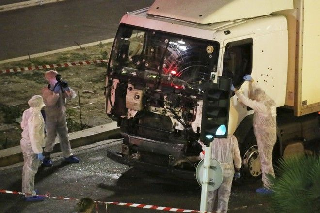 2016 AP YEAR END PHOTOS - Authorities investigate a truck after it plowed through Bastille Day revelers in the French resort city of Nice, France, on July 14, 2016. France was ravaged by its third attack in two years when a large white truck mowed through revelers gathered for Bastille Day fireworks in Nice, killing dozens of people as it bore down on the crowd for more than a mile along the Riviera city's famed seaside promenade. (Sasha Goldsmith via AP, File)
