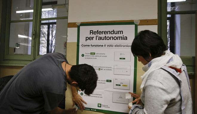 Scrutineers fix a poster at the Berchet School polling station, in Milan, Italy, Saturday, Oct. 21, 2017. It is greater autonomy, not independence, that two of Italy's wealthiest regions are seeking in a pair of referendums Sunday, yet Catalonia's secessionist ambitions loom over the debate. The president of Lombardy, Roberto Maroni and Veneto, Luca Zaia, are campaigning on the economic benefits of loosening Rome's grip. (AP Photo/Luca Bruno)