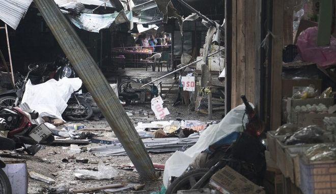 Villagers watch the site of a bombing at a market in Yala province, southern Thailand. Monday, Jan. 22, 2018. Police say a few people have been killed by the explosion. (AP Photo/Somphop Suphanaranond)