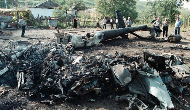 Local residents look at the debris of a Mi-24 military helicopter shot down during a fighting with rebels in the village of Galashki, 100 kilometers (62 miles) south of Nazran, in the Russian republic of Ingushetia near the border with Chechnya, Thursday, Sept. 26, 2002. Two crewmen were killed. The outbreak of fighting in Ingushetia represents a widening of the battleground of the Chechen war, which has largely been confined to the borders of Chechnya.(AP Photo/Musa Sadulayev)