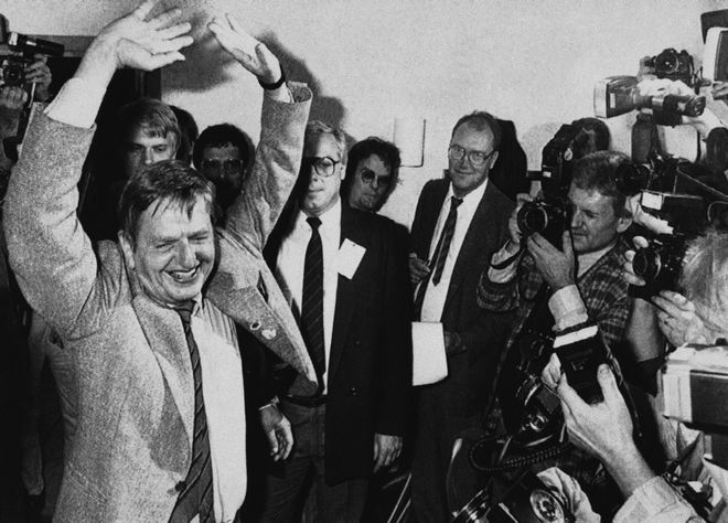 Cornered by photographers, Olof Palme, Chairman of the Swedish Social Democratic Party and winner of the general election, hoists his arms in joy and as a sign of victory after votes was counted and the result showed that he will remain as Prime Minister in Stockholm on Sunday, Sept. 15, 1985. (AP Photo/Borje Thuresson)