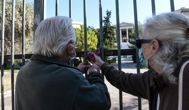 Ηλικιωμένοι αποτίουν φόρο τιμής, αφήνοντας λουλούδια στην πύλη του Πολυτεχνείου