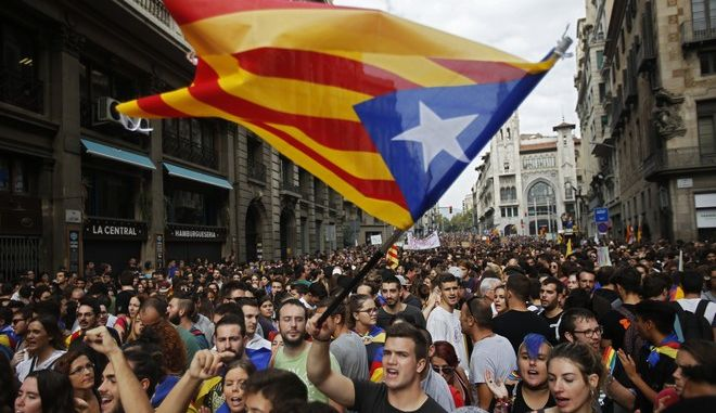 """Demonstrators with """"estelada"""", or Catalonia independent flag, gather in protest in front of the Spanish police station in Barcelona, Spain, Tuesday, Oct. 3, 2017. Labor unions and grassroots pro-independence groups are urging workers to hold partial or full-day strikes and demonstrations throughout Catalonia to protest alleged brutality by police during a referendum on the region's secession from Spain that left hundreds of people injured. (AP Photo/Francisco Seco)"""
