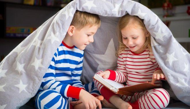 Δύο αδέρφια διαβάζουν ένα βιβλίο