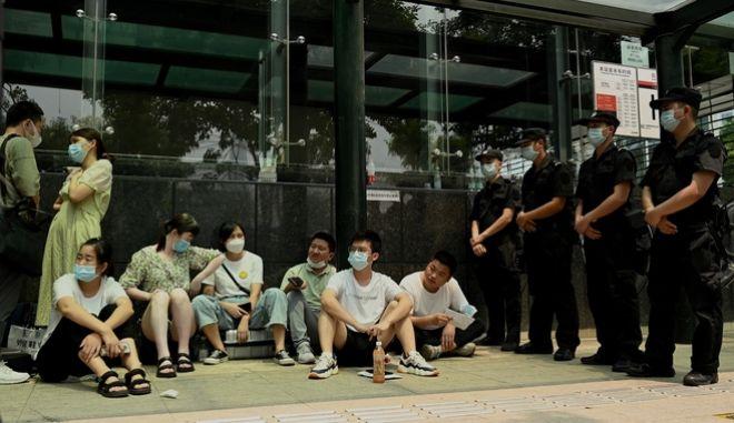 Κόσμος και αστυνομία έξω από τα κεντρικά της Evergrande