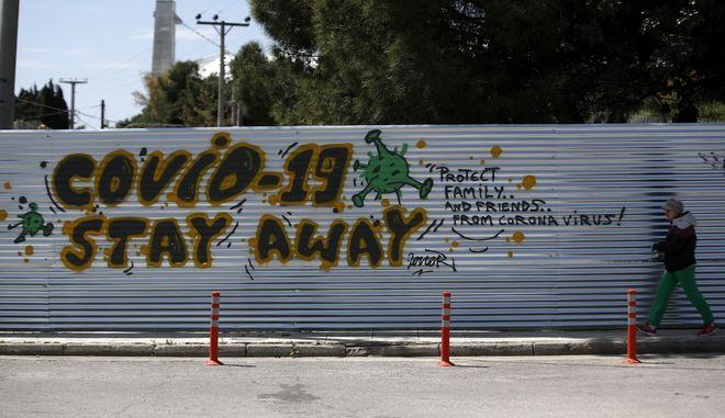 Άνδρας μπροστά από γκράφιτι με θέμα τον κορονοϊό στην Αθήνα