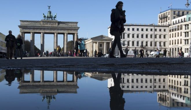 The Brandenburg Gate reflected by a puddle on Pariser Platz  Square  in Berlin, Germany, Tuesday, Nov. 7, 2017.  (Ralf Hirschberger/dpa via AP)
