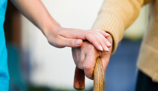 Γιατρός κρατά το χέρι ασθενούς με Αλτσχάιμερ