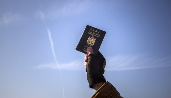 A refugee holds up his Iraqi passport at the port of Molyvos after a rescue operation by members of the Frontex, European Border Protection Agency, from Portugal near the northeastern Greek island of Lesbos, Tuesday, Dec. 8, 2015. Greece is the main point of entry into the EU for people fleeing war and poverty at home, with the vast majority of the 700,000 people who have entered the country this year reaching Greek islands from the nearby Turkish coast. (AP Photo/Santi Palacios)