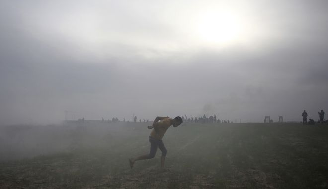 A Palestinian protester runs for cover from teargas fired by Israeli troops during clashes on the Israeli border with Gaza, Friday, Dec. 22, 2017. (AP Photo/ Khalil Hamra)