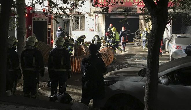 In this photo provided by China's Xinhua News Agency, firefighters work at the site of a fire in Daxing district of Beijing, capital of China, Sunday, Nov. 19, 2017.  The official Chinese news agency says a fire at a building advertising low-cost rental apartments in a southern Beijing suburb has killed more than a dozen of people.(Luo Xiaoguang/Xinhua via AP)