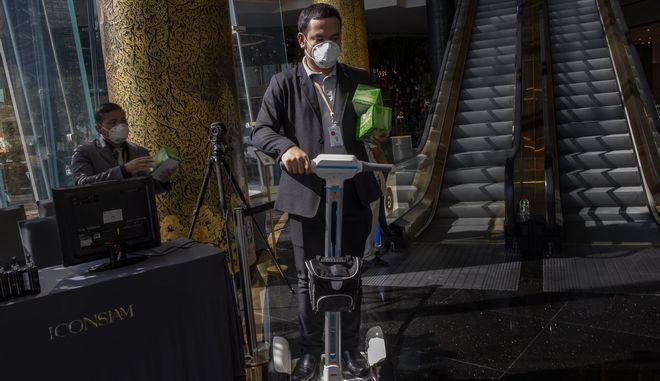 Άνδρας με αερόσακους φέρει προστατευτικές μάσκες προσώπου για διανομή