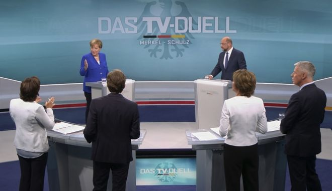 The screenshot provided by RTL shows German Chancellor Angela Merkel, background left, of the Christian Democratic party, and her challenger Martin Schulz, background right, of the Social Democratic party as they answer questions of the journalists, front row from left, Sandra Maischberger, Claus Strunz, Maybrit Illner and Peter Kloeppel during the only TV debate three weeks before the German parliament elections in a TV studio in Berlin Sunday, Sept. 3, 2017. (RTL via AP)