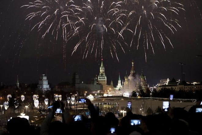 People take pictures as fireworks explode over the Kremlin, during New Year celebrations in Moscow, Russia, Monday, Jan. 1, 2018. New Year is Russia's major gift-giving holiday. (AP Photo/Denis Tyrin)