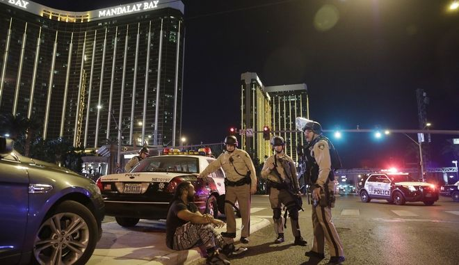 FILE - In this Sunday, Oct. 1, 2017 file photo, police officers stand at the scene of a mass shooting near the Mandalay Bay resort and casino on the Las Vegas Strip, in Las Vegas. A revised chronology given by investigators for the Las Vegas massacre is intensifying pressure for police to explain how quickly they responded to what would become the deadliest mass shooting in modern U.S. history. (AP Photo/John Locher, File)