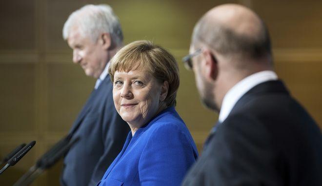 La canciller alemana Angela Merkel sonríe al líder del partido Social Demócrata Martin Schulz, mientras atrás aparece el gobernador de Bavaria Horst Seehofer antes de una rueda de prensa después de conversaciones exploratorias entre el bloque conservador de Merkel y los socialdemócratas hacia la formación de un nuevo gobierno alemán, el viernes 12 de enero de 2018 en Berlín. (Bernd von Jutrczenka/dpa vía AP)