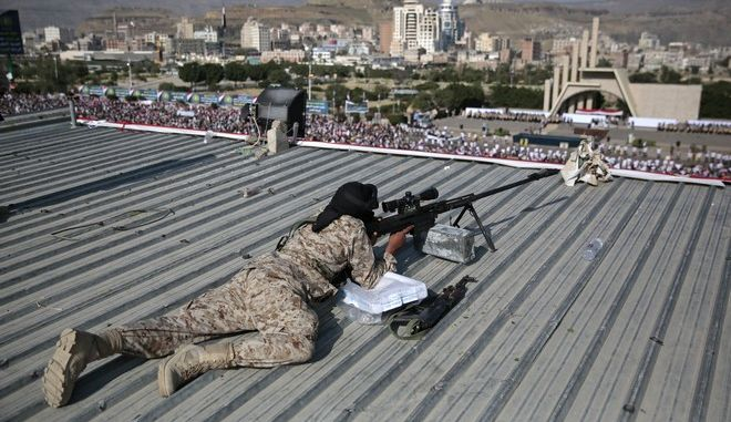 A Houthi Shiite sniper keeps watch over a rally to mark the third anniversary of the Houthis' takeover of the Yemeni capital, in Sanaa, Yemen, Thursday, Sept. 21, 2017. Abdel-Malek al-Houthi, the leader of Yemen's Shiite rebels lashed out in a defiant speech broadcast Wednesday, the eve of the anniversary of the day his forces stormed into Sanaa. Al-Houthi accused the U.S., Saudi Arabia and the UAE of seeking to divide Yemen. (AP Photo/Hani Mohammed)