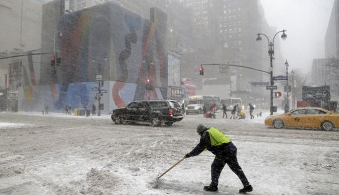 A man tries to clear snow at the intersection of Eighth Ave. and 34th St. in New York, Thursday, Jan. 4, 2018. Residents across a huge swath of the U.S. awakened Thursday to the beginnings of a massive winter storm expected to deliver snow, ice and high winds followed by possible record-breaking cold as it moves up the Eastern Seaboard from the Carolinas to Maine. (AP Photo/Seth Wenig)