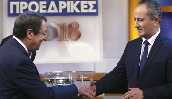 Presidential candidates Cyprus' President Nicos Anastasiades, left, and Stavros Malas, who is backed by the left-wing AKEL party, shake hands before their live televised debate in capital Nicosia, Cyprus, Wednesday, Jan. 31, 2018. Cypriots will vote on Sunday Feb. 4, for the second round in presidential elections with critical topics including the reunification of the divided island and economic recovery. (AP Photo/Petros Karadjias)