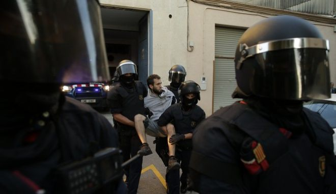 Regional police officers remove a protestor during a protest against a search for propaganda supporting Catalonia's independence referendum at the private postal service company Unipost in Terrassa, Spain, Tuesday, Sept. 19, 2017. The Spanish government has vowed to stop the planned Oct. 1 vote that it calls illegal. But Catalonia's leaders have pushed ahead even after Spain's Constitutional Court suspended the law passed by Catalonia's regional parliament that convoked the referendum. (AP Photo/Manu Fernandez)