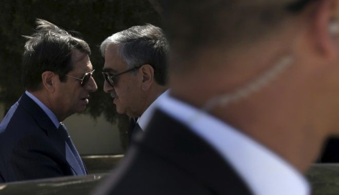 FILE - In this Wednesday, Sept. 14, 2016 file photo, Cypriot President Nicos Anastasiades, left, and breakaway Turkish Cypriot leader Mustafa Akinci, right, talk as a guard stands in front of a car after their meeting aimed at reunifying the ethnically divided island, at the disused Nicosia airport inside a United Nations controlled buffer zone in this divided island of Cyprus. A United Nations spokesman says on Wednesday, Oct. 27, 2016, the leaders of ethnically divided Cyprus' Greek and Turkish speaking communities will conduct a key phase of reunification talks in Mont Pelerin, Switzerland next month Nov. 7-11. Aleem Siddique said the talks between Anastasiades and Akinci will focus on how much territory each side will administer under an envisioned federation.  (AP Photo/Petros Karadjias, File)